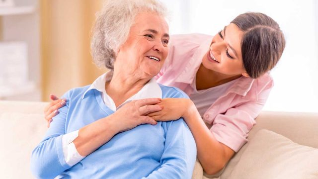 nurse laughing with a senior woman